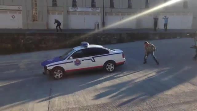 Grabación de la escena de la serie de Antena 3 Allí abajo en el que un coche la policia de precipita alagua.