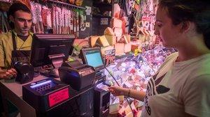 Una clienta paga en una de las tiendas Germans Gracia de Barcelona en una máquina que devuelve el cambio.