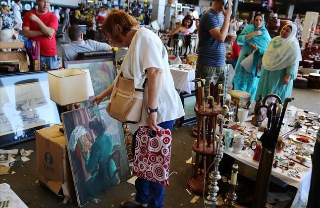 Una compradora dels Encants valora un retrat de la mare dAlbert Ràfols-Casamada.