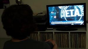 Una mujer mira en televisión la noticia sobre la disolución de ETA.