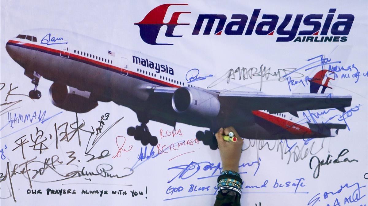 Una mujer escribe un mensaje de solidaridad con los pasajeros del vuelo desaparecido de Malaysia Airlines en Kuala Lumpur en el 2014.