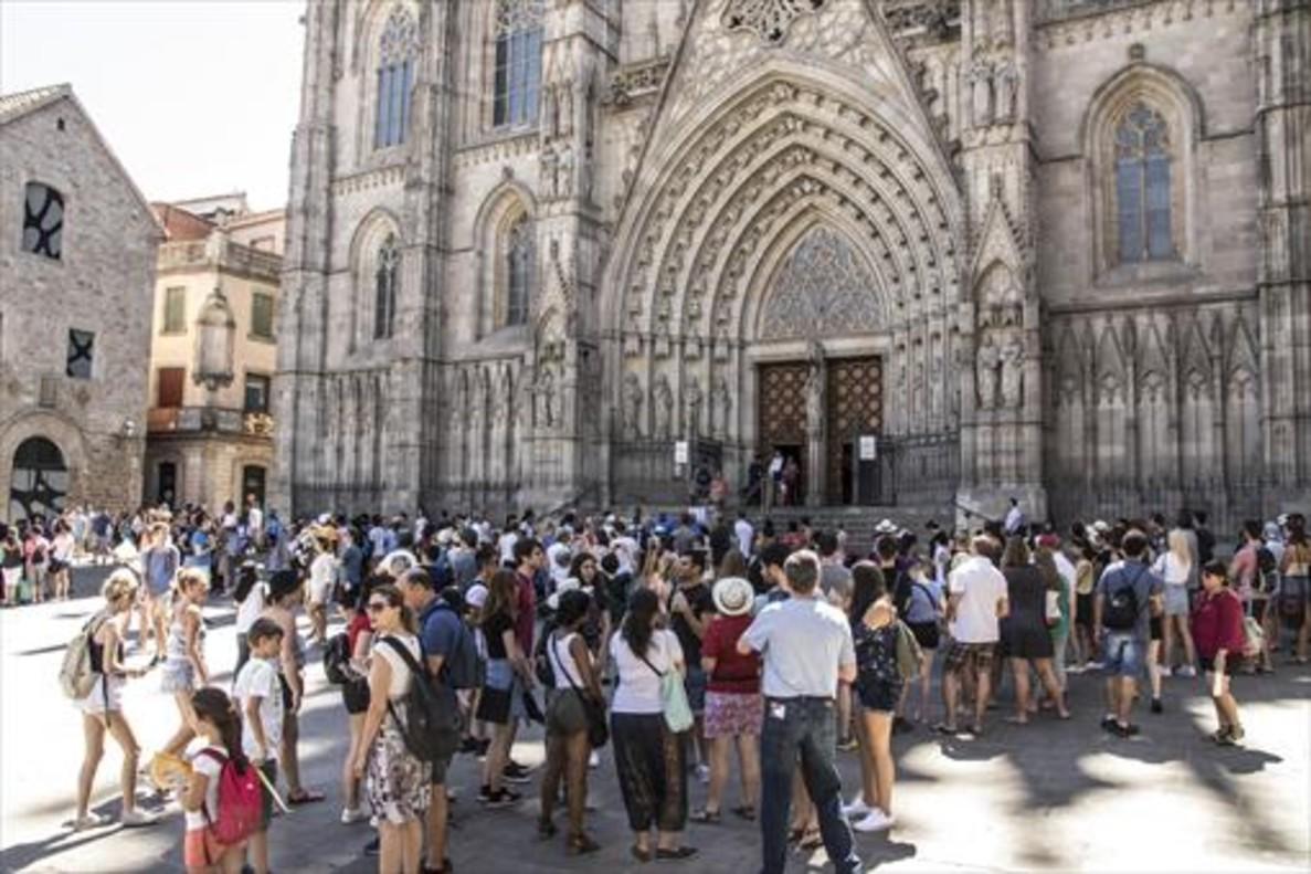 Una multitud de turistas se concentra ante la Catedral de Barcelona.