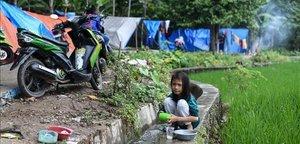 Una niña lava los platos en un campamento para desplazados por el tsunami en Rajabasa, en la provincia indonesia de Lampung.
