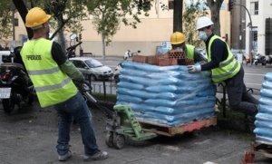 Varios obreros empujan material de construcción necesario para rehabilitar un edificio, en Madrid, el lunes pasado.