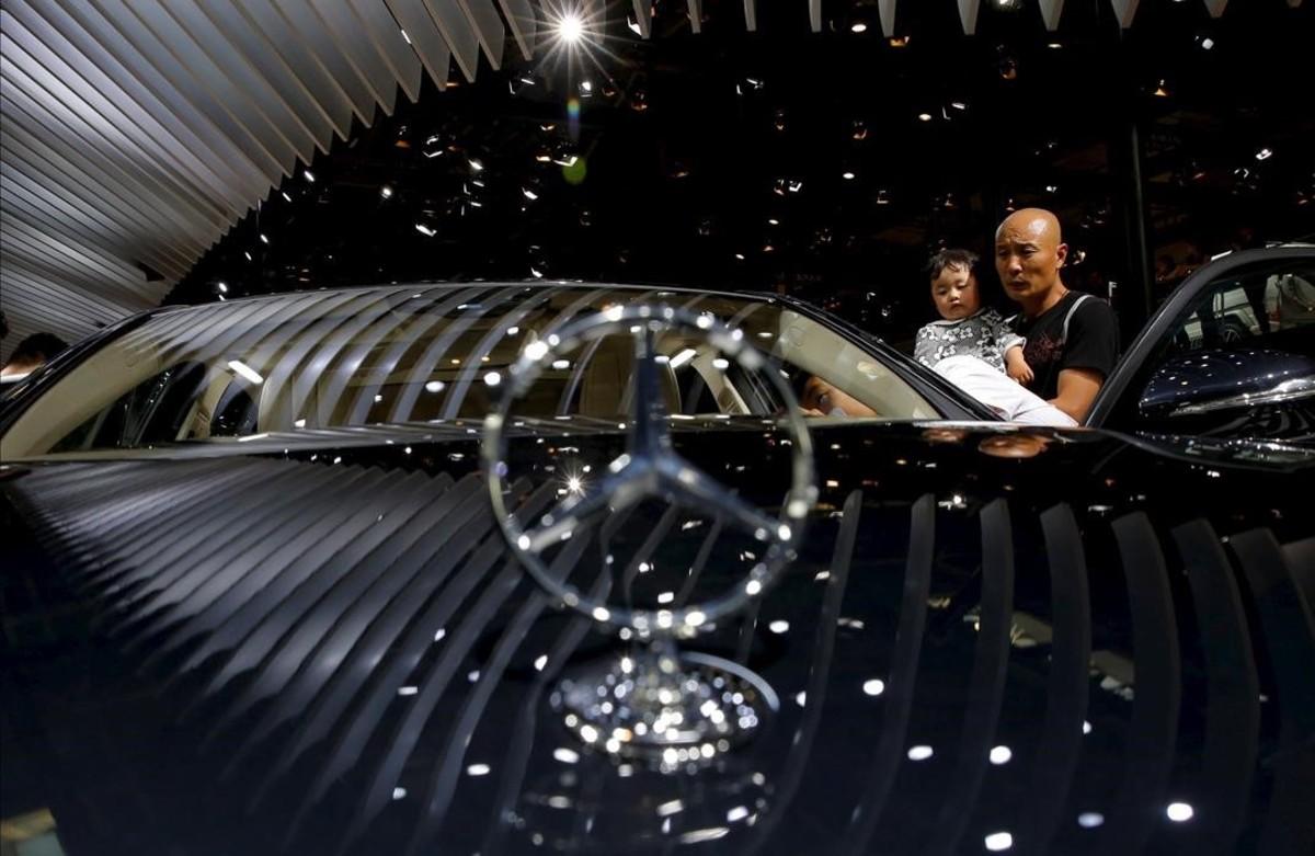 Visitantes del Salón del Automóvil de Pekín observanun Mercedes-Benz E320 Sedan s modelo L 4MATIC.