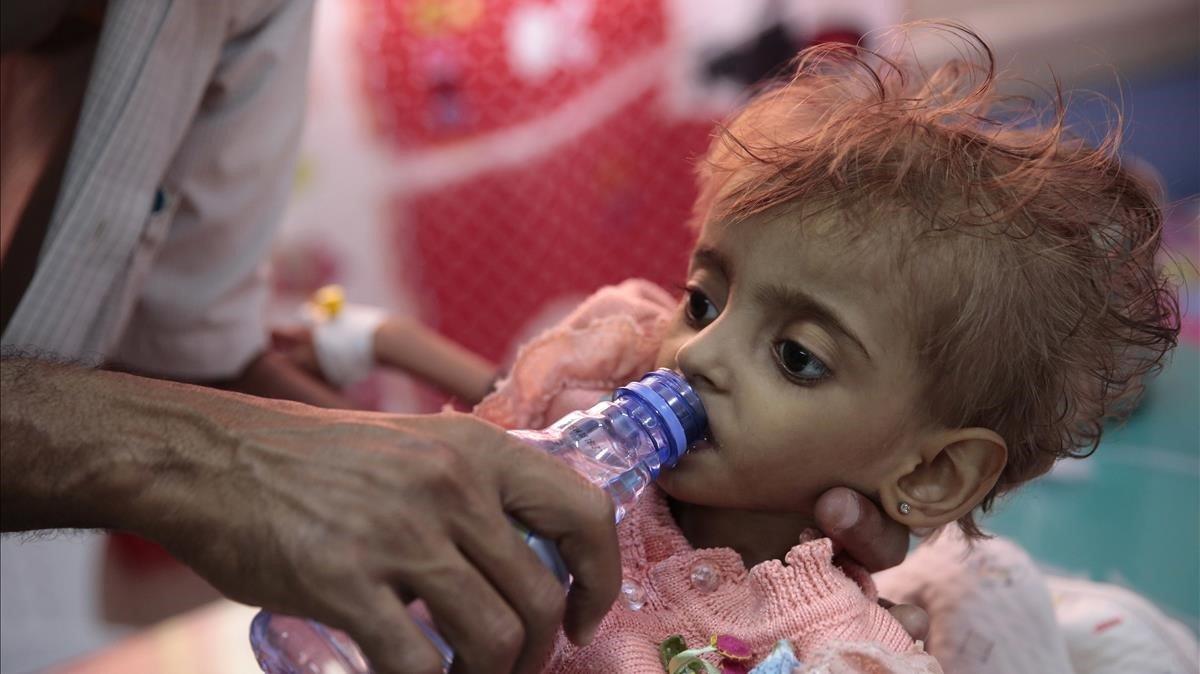 Un padre da de beber a su hija desnutrida el pasado mes de septiembreen un centro hospitalario deHodeida, ciudad bombardeada por Arabia Saudí y sus aliados.