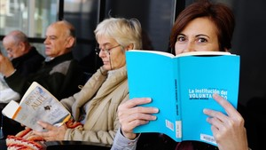Una voluntaria de lectura a domicilio en voz alta para gente con problemas de visión o movilidad.