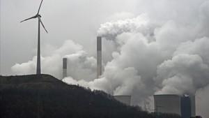 Un aerogenerador eólico delante de las torres de ventilación de la central térmica de Gelsenkirchen, en el estado alemán de Renania del Norte-Westfalia.