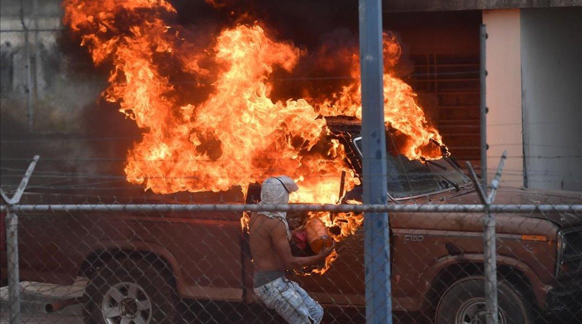 Vehículo en llamas junto a una comisaría policial venezolana en el estado de Roraima, en la frontera con Brasil.