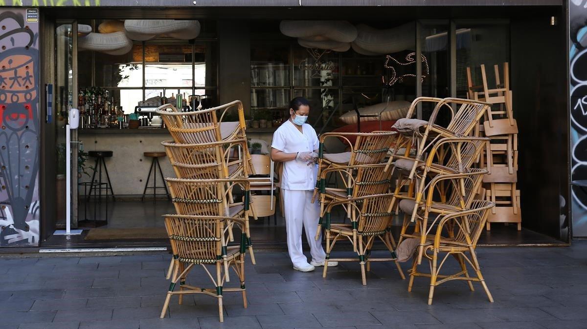Un bar de Barcelona, con las sillas apiladas de la terraza.