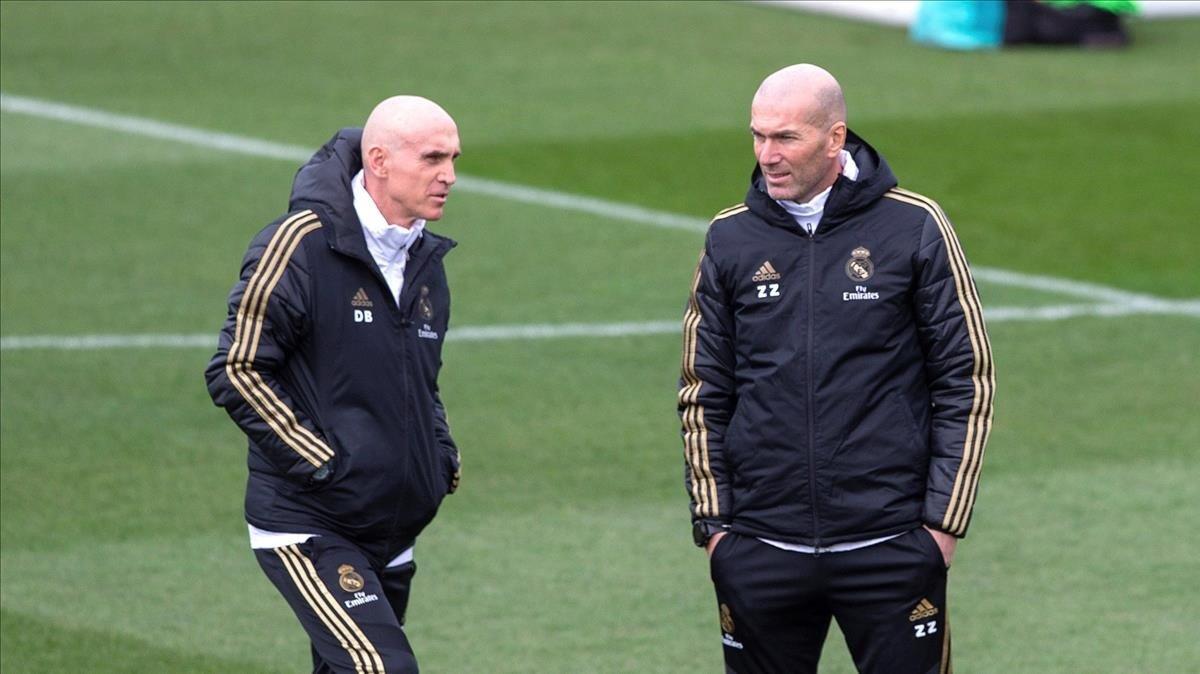 Zinedine Zidane (derecha) charla con su asistente, David Bettoni, en el último entrenamiento del Madrid antes de viajar a Vitoria.