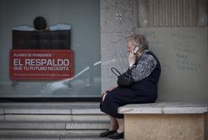 Una mujer mayor habla por teléfono móvil al lado de un cartel de planes de pensiones.