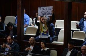 La activista Lilian Tintori, esposa del arrestado opositor venezolano Leopoldo López, muestra una pancarta contra Maduro en la Asamblea Nacional de Venezuela.
