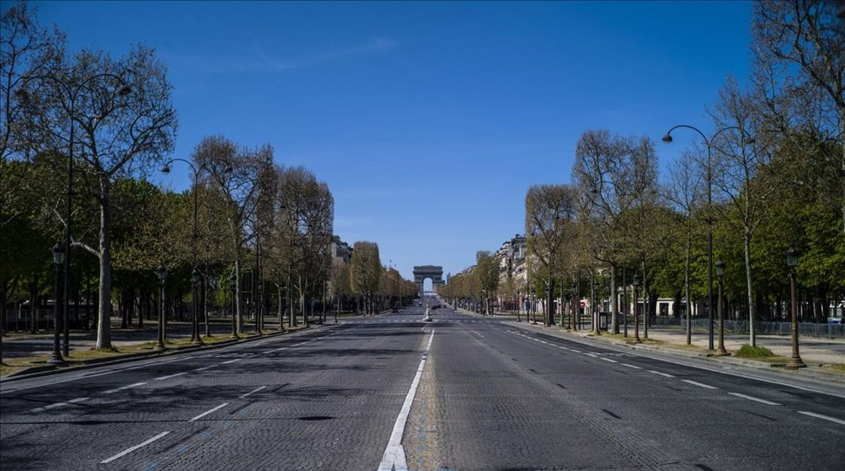 La avenida de los Campos Elíseos deParís, con el arco de triunfo al fondo, completamente vacía.