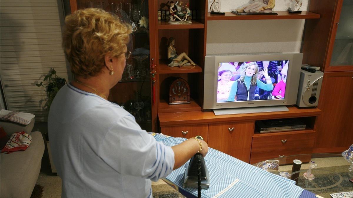 Una ama de casa sigue un programa de televisión mientras trabaja en el hogar.