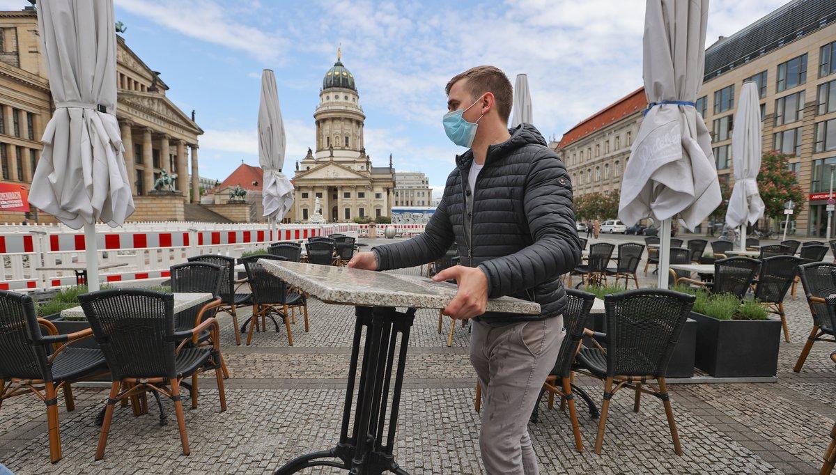 Un trabajador de un restaurante en Berlín reorganiza las mesas, ante la falta de clientes.