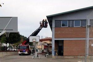 Bomberos retiran lazos amarillos en el colegio electoral La Cooperativa de Sarrià de Ter.