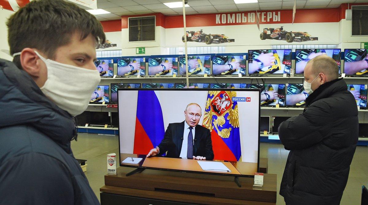Clientes en una tienda observan la rueda de prensa del presidente Putin.