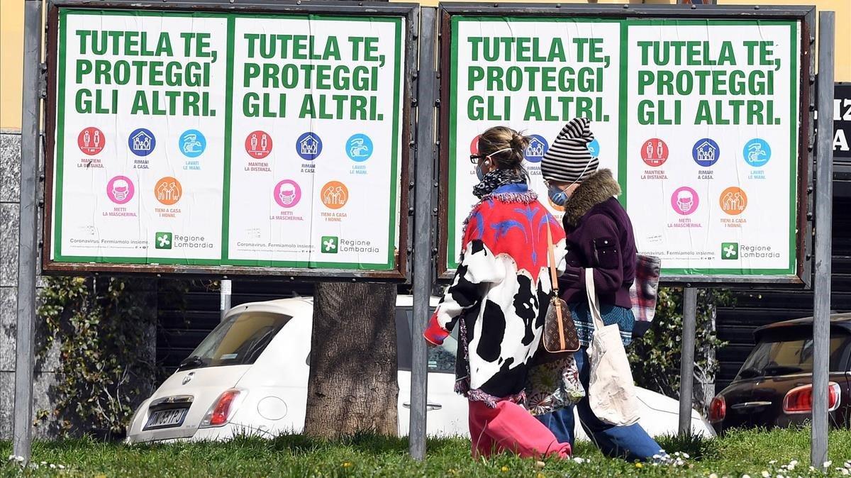 Dos mujeres con mascarillas caminan frente a unos carteles que instan a los ciudadanos a protegerse frente al coronavirus, este miércoles en Milán.