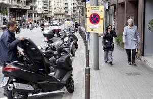 Espacio habilitado para motos y servicios sobre el asfalto de la calle de Balmes, en Barcelona.