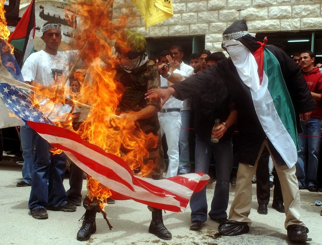 Estudiantes palestinos quemando una bandera de Estados Unidos durante una manifestación anti-israelí en la universidad de Hebrón, en la región de Cisjordania.