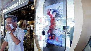 Un hombre con mascarilla pasa junto a un anuncio de 'Mulán'ante un cine de Hong Kong, la pasada semana.