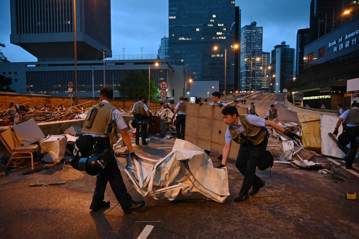 Policías de Hong Kong retiran las barricadas de las protestas en el distrito financiero.