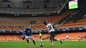 Ilicic y Kondogbia disputan un balón en el Valencia-Atalanta disputado a puerta cerrada.