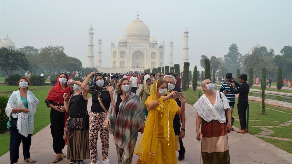 Un grupo de turistas se cubren la boca con una máscara mientras visitan elTaj Mahal bajo una nuve de contaminación.