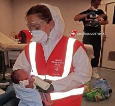 Miembros de la Guardia Costera italiana alimentan a bebés recién nacidos que han sido rescatados ante las costas de Libia.