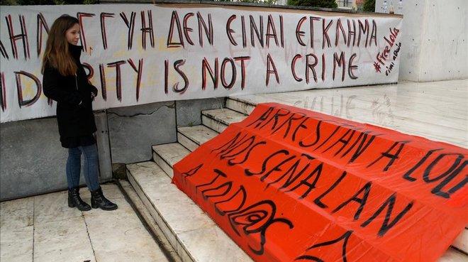 Laura Gómez, hija de Lola Gutiérrez, junto a pancartas de la red de apoyo a la activista.