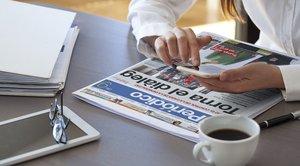 Una lectora llegeix el diari en mòbil i paper.