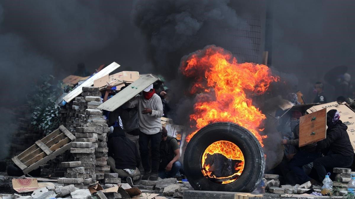 Manifestantes se cubren tras varias barricadas mientras se enfrentan a la policía en el décimo día de de protestas contra el Gobierno de Lenín Moreno.