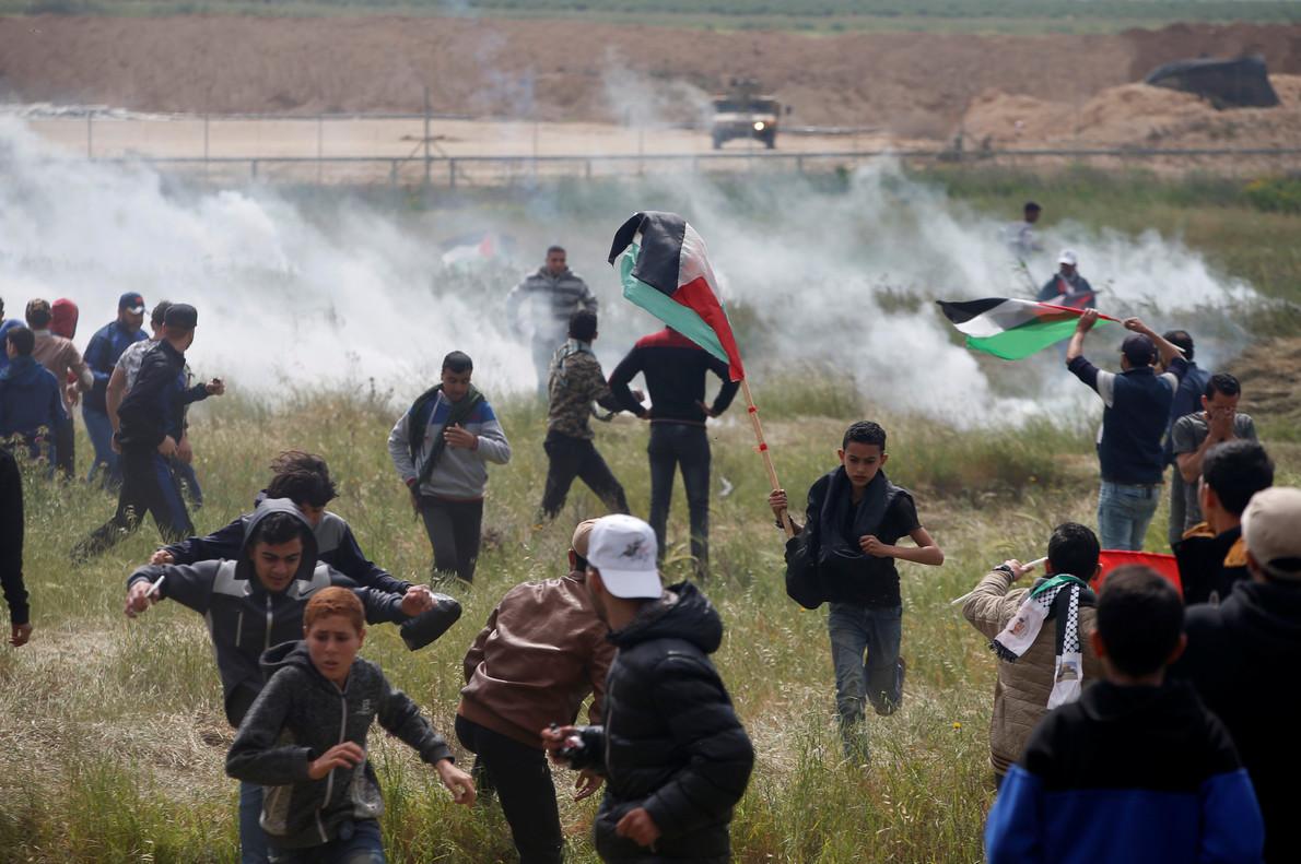 Manifestantes palestinos huyen de los disparos de gas del Ejército israelí, junto a la frontera.
