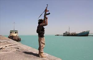 Un militar de las fuerzas gubernamentales respaldadas por Arabia Saudí levanta su arma frente al Mar Rojo, dominado por el otro lado por los huties.