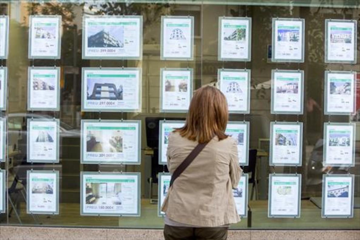 Una mujer mira ofertas de compra y alquiler de viviendas.