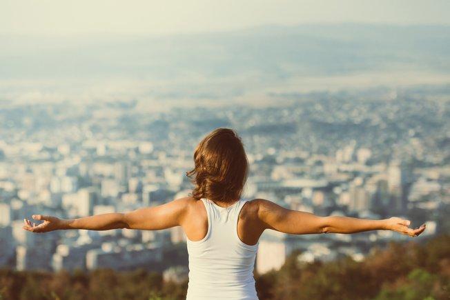 Mujer con los brazos extendidos frente a una ciudad.