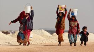 Mujeres sirias cuyas familiares han huido de los bombardeos en Idleb y la zona de Alepo cargan con cubos improvisados de agua, en un campamento de desplazados cerca de Bab al-Hawa, junto a la frontera sirioturca, el 22 de enero.