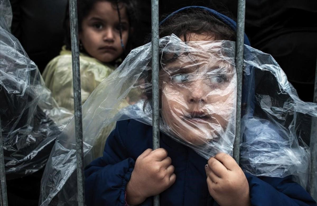 Niños refugiados tapados con plásticos para refugiarse de la llulvia esperan para registrarse en Serbia.Es una de las imágenes premiadas en el World Press Photo.