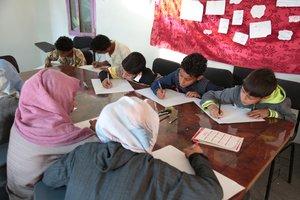 Niños y niñas en un espacio seguro de Save the Children en Saná redactando su resolución ideal para la guerra en Yemen.