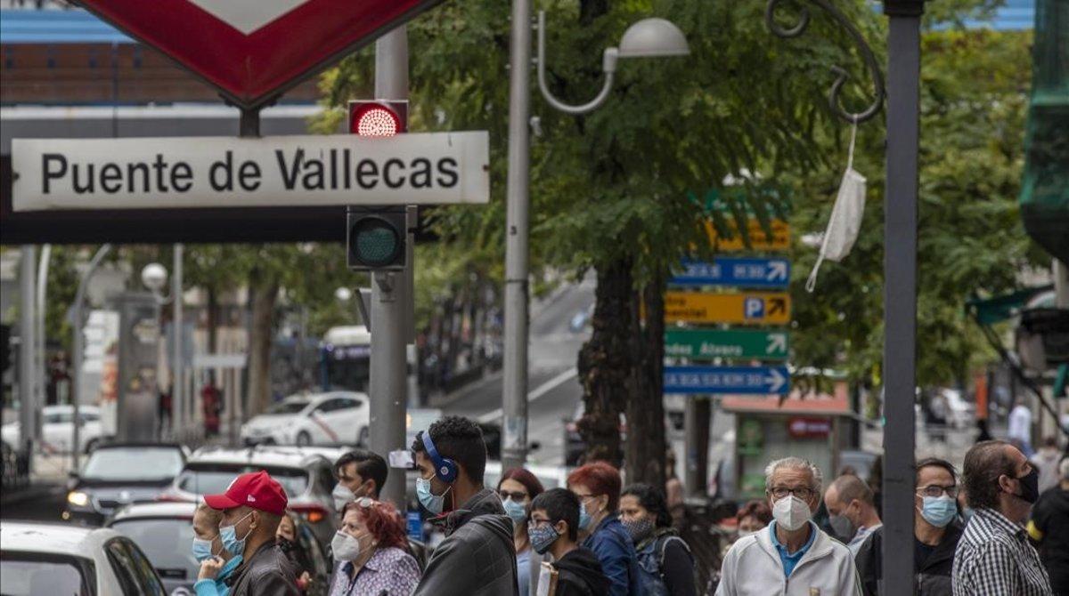 Peatones ante el metro de Puente de Vallecas, en Madrid.