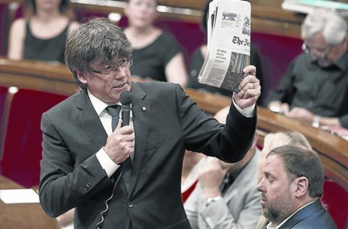 Puigdemont muestra un ejemplar de The New York Times en el Parlament.