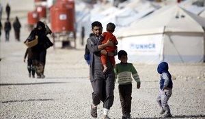 Un refugiado iraquí que huyó de Mosul lleva a su hijo mientras camina en el campamento deAl-Hol