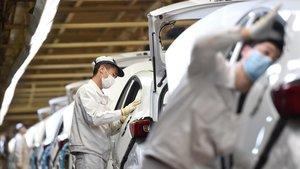 Trabajadores con mascarilla en la línea de ensamblaje de la planta de Dongfeng Honda de Wuhan, este lunes.