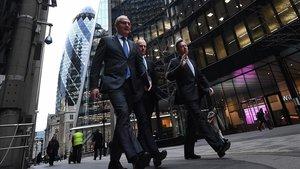Tres hombres caminan por el centro financiero de Londres, este jueves.