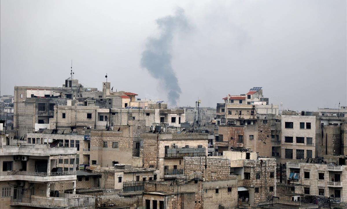 Una columna dehumo se eleva sobre los escombrosdurante un bombardeo de las fuerzas gubernamentales sirias en Sarman, en Idlib.