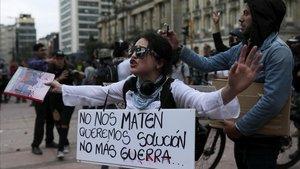 Una manifestante muestra una pancarta reivindicativa, este sábado, en Bogotá.
