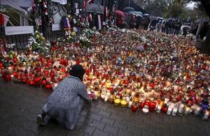 La muchacha pone velas para conmemorar a las víctimas de los ataques en París frente a la embajada francesa en Varsovia