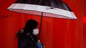 Una mujer camina bajo la lluvia con mascarillas y guantes, el pasado 23 de marzo, noveno día de confinamiento.