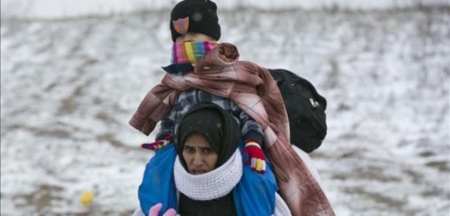 Una mujer camina con su hijo a cuestas entre temperaturas gélidas en Serbia, este lunes.